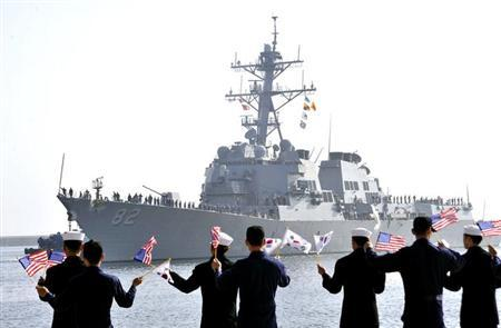 The guided missile destroyer USS Lassen (DDG 82) arrives as South Korean navy sailors wave South Korean and U.S. national flags at a South Korean naval port in Donghae, about 190 km (118 miles) east of Seoul, March 9, 2013 in this photo provided by South Korean Navy. REUTERS/South Korean Navy/Handout
