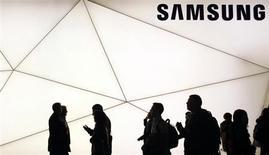 Люди проходят мимо стенда Samsung на Всемирном мобильном конгрессе в Барселоне, 25 февраля 2013 года. Samsung Electronics, главный соперник Apple Inc, ждет, что операционная прибыль за январь-март вырастет на 53 процента в годовом выражении до 8,7 триллиона вон ($7,7 миллиарда) благодаря продажам средних по стоимости смартфонов. REUTERS/Albert Gea