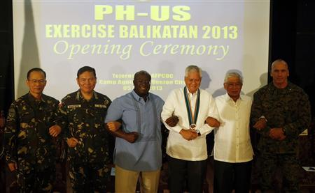 Philippine foreign secretary Albert del Rosario (3rd-R) and U.S. ambassador to the Philippines Harry Thomas (3rd-L) link arms with other military officials during the opening ceremony of annual Philippines-U.S. military exercise dubbed as ''Balikatan'' (shoulder to shoulder) at Camp Aguinaldo in Quezon city, Metro Manila April 5, 2013. REUTERS/Erik De Castro