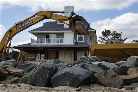 Heavy machinery moves large rocks to build a new sea wall nearly five months after the landfall of Superstorm Sandy in Bay Head, New Jersey, March 22, 2013. REUTERS/Lucas Jackson