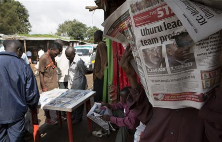 A man reads the morning edition of The Standard newspaper showing provisional results for the two main presidential election contenders in the Kibera slum of Nairobi, March 8, 2013. REUTERS/Julia Sestier