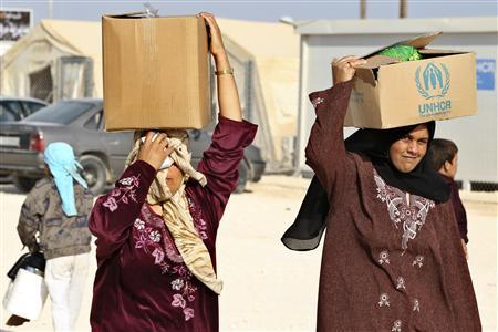 Syrian refugees carry aid and ration at the Zaatari refugee camp in the Jordanian city of Mafraq, near the border with Syria October 22, 2012. REUTERS/Muhammad Hamed