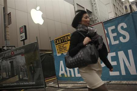 A woman walks past an Apple logo at the company's flagship retail store near signs for the central subway project in San Francisco, California January 23, 2013. REUTERS/Robert Galbraith