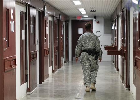 A guard walks through a cellblock inside Camp V, a prison used to house detainees at Guantanamo Bay U.S. Naval Base, March 5, 2013. REUTERS/Bob Strong
