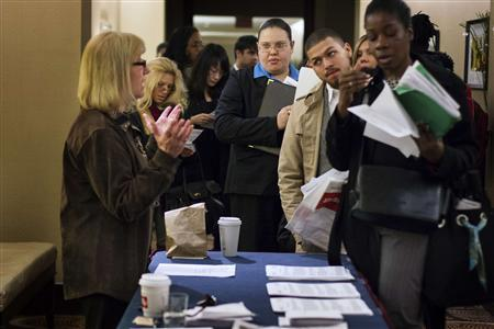 Job seekers adjust their paperwork as they wait in line to attend a job fair in New York in this file photo taken February 28, 2013. REUTERS/Lucas Jackson/Files