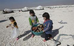 Дети из Сирии в лагере беженцев Заатари в Иордании 21 февраля 2013 года. ООН предупредила в пятницу, что вскоре израсходует все средства, отпущенные на беженцев из охваченной кровопролитием Сирии, поток которых в соседние Иорданию, Ливан, Ирак и Турции лишь растёт. REUTERS/Ali Jarekji