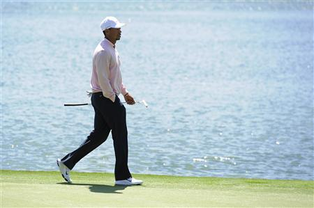 Tiger Woods of the U.S. walks along the 12th green during the 2013 Tavistock Cup golf tournament at Isleworth Golf and Country Club in Windermere, Florida March 26, 2013. REUTERS/Scott Miller