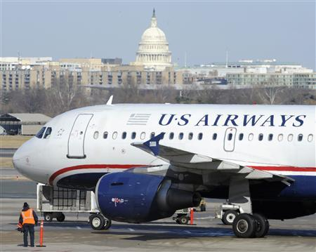 A US Airways plane arrives at the Ronald Reagan Washington National Airport in Arlington County, Virginia February 10, 2013, as negotiations continue this week between parent companies US Airways Group Inc and AMR Corp on a possible $11 billion merger, creating what would be the world's largest airline. The U.S. Capitol is seen in the background. REUTERS/Mike Theiler