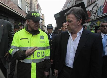 Colombian President Juan Manuel Santos (R) talks with Colombian Police Chief General Jose Leon Riano during a visit to the ''El Bronx'' district after a security meeting in Bogota April 1, 2013. REUTERS/John Vizcaino