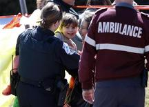 A police officer hands a child to a caregiver near the scene of a shooting in Gatineau, Quebec April 5, 2013. REUTERS/Blair Gable