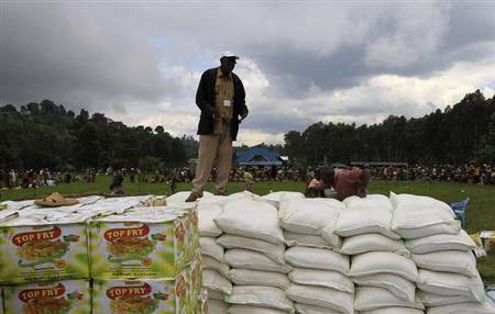 A worker stands on piles of relief food items provided by Oxfam International in an area under controlled of Congolese Revolutionary Army (CRA), in Chengerero, eastern Democratic Republic of Congo November 3, 2012. REUTERS/James Akena