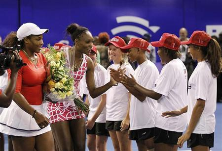 U.S. tennis players Serena Williams (L) and her sister Venus greet children at the end of their exhibit tennis match in Johannesburg November 4, 2012. REUTERS/Siphiwe Sibeko
