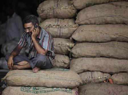A shopkeeper speaks on a mobile phone at a vegetable wholesale market in Mumbai June 8, 2010. REUTERS/Rupak De Chowdhuri/Files