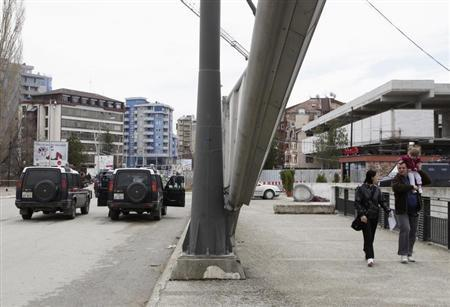 Pedestrians pass by an Italian Carabinieri on the main bridge in the ethnically divided town of Mitrovica, April 3, 2013. REUTERS/Hazir Reka
