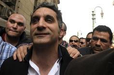 Bassem Youssef, humorista mais conhecido do Egito, gesticula para jornalistas e ativistas ao chegar em tribunal no Cairo, Egito. Um tribunal egípcio rejeitou neste sábado uma ação judicial que pedia o banimento da TV de um popular humorista acusado de insultar o presidente e a religião muçulmana, mas ele ainda é alvo de uma investigação criminal por denúncias semelhantes. 31/03/2013 REUTERS/Mohamed Abd El Ghany