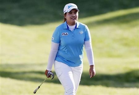 Inbee Park of South Korea smiles as she is applauded by the crowd while walking to her ball on the 17th green during the third round of the Kraft Nabisco Championship LPGA golf tournament in Rancho Mirage, California, April 6, 2013. REUTERS/Danny Moloshok