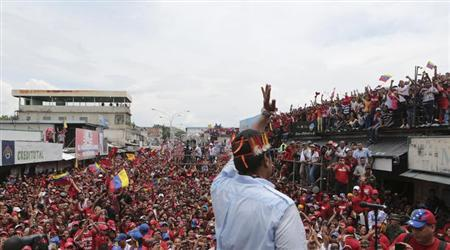 Venezuela's acting President and presidential candidate Nicolas Maduro wearing a feather headgear greets supporters during a campaign rally at the state of Amazonas, in this picture provided by Miraflores Palace on April 6, 2013. Venezuelans will hold presidential elections on April 14. REUTERS/Miraflores Palace/Handout