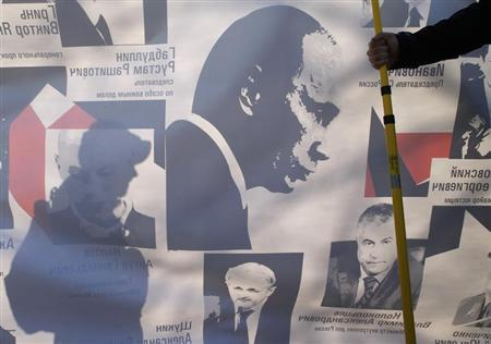 Demonstrators hold a banner with a picture of Russia's President Vladimir Putin (C) during a rally held by opposition supporters in St. Petersburg, April 6, 2013. REUTERS/Alexander Demianchuk