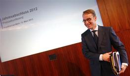 Jens Weidmann, President of Germany's federal reserve bank Bundesbank smiles as he takes his papers after the bank's annual news conference in Frankfurt, March 12 2013. REUTERS/Kai Pfaffenbach