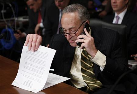 Senator Charles Schumer looks through his prepared remarks before introducing Jack Lew, President Barack Obama's nominee to lead the Treasury Department, before a Senate Finance Committee confirmation hearing on Capitol Hill in Washington February 13, 2013. REUTERS/Kevin Lamarque