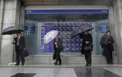 Pedestrians holding umbrellas stand in front of a stock index board showing various stock prices outside a brokerage in Tokyo April 3, 2013. REUTERS/Yuya Shino