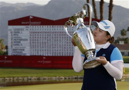 Inbee Park of South Korea kisses her trophy while posing in front of the leaderboard after winning the Kraft Nabisco Championship LPGA golf tournament in Rancho Mirage, California, April 7, 2013. REUTERS/Danny Moloshok