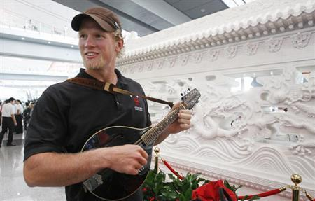 (File photo) Canadian rower Adam Kreek plays an instrument as he waits for an elevator after arriving at the Beijing airport to take part in the Beijing 2008 Olympic Games, August 4, 2008. REUTERS/Shaun Best