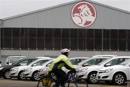 A cyclist rides past a General Motors (GM) Holden storage facility in Melbourne June 2, 2009. REUTERS/Mick Tsikas (AUSTRALIA TRANSPORT BUSINESS) - RTR246F6