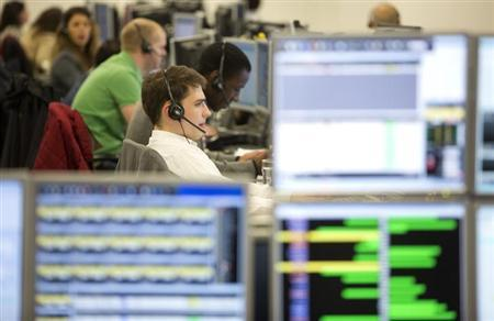 Traders take telephone calls on the IG Group trading floor in London March 18, 2013. REUTERS/Neil Hall/Files