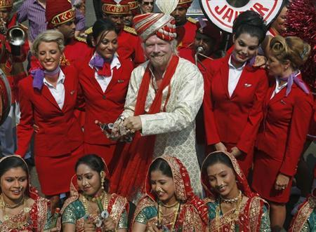 Virgin Group founder Richard Branson poses with his crew members and a group of Indian folk artists (bottom) during a promotional event in Mumbai October 26, 2012. REUTERS/Danish Siddiqui