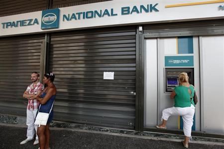 A woman makes a transaction outside a closed branch of the National Bank of Greece during a 24-hour strike by bank employees in Athens July 30, 2012. REUTERS/Yorgos Karahalis