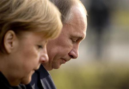 German Chancellor Angela Merkel and Russian President Vladimir Putin lay a wreath at the Cemetery of Honour on the north bank of the Maschsee Lake in Hanover April 8, 2013. REUTERS/Odd Andersen/Pool