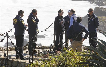 Police officers and forensic experts inspect the tomb of Chilean poet and Nobel laureate Pablo Neruda inside the grounds his house-museum before the exhumation of his remains in the coastal town of Isla Negra, about 106 km (66 miles) northwest of Santiago April 7, 2013. REUTERS/Eliseo Fernandez
