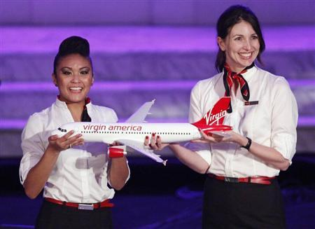 Virgin America flight attendants hold a model of a Virgin America Airbus A320 commercial aircraft during a live auction where two bidders each paid $50,000 for the opportunity for each of them to name a Virgin America airplane at Richard Branson and Eve Branson's Rock the Kasbah Gala to benefit Virgin Unite and the Eve Branson Foundation at Vibiana in Los Angeles, October 26, 2009. REUTERS/Danny Moloshok