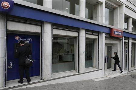 A man makes a transaction at an ATM machine outside a Eurobank branch in central Athens April 8, 2013. REUTERS/John Kolesidis