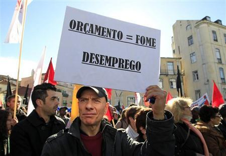 A man holds a sign reading: ''Budget = hunger, unemployment'' during an anti-austerity protest in front of Portugal's parliament in Lisbon November 27, 2012. REUTERS/Jose Manuel Ribeiro