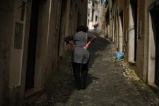 A woman walks at Alfama neighbourhood in Lisbon April 8, 2013. REUTERS/Rafael Marchante