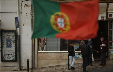 People chat near a Portuguese flag in downtown Lisbon April 8, 2013. REUTERS/Rafael Marchante