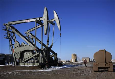 A man walks past a Lufkin oil drilling pump in McKenzie County outside of Williston, North Dakota in this file photo taken March 12, 2013. General Electric Co said it will buy oilfield services provider Lufkin Industries Inc for about $2.98 billion to boost its presence in the energy business. REUTERS/Shannon Stapleton/Files
