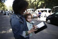 A woman carrying a child looks at an iPad tablet after the Emporio Armani Spring/Summer 2013 collection at Milan Fashion Week September 20, 2012. REUTERS/Stefano Rellandini