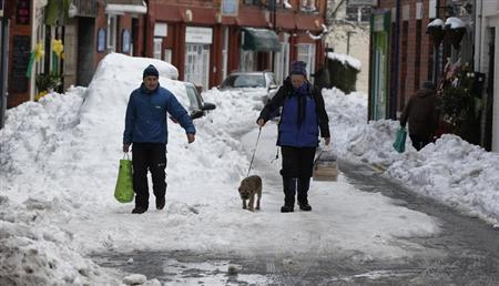 People carry shopping bags down a snow covered street in Llangollen, north Wales, March 25, 2013. REUTERS-Phil Noble