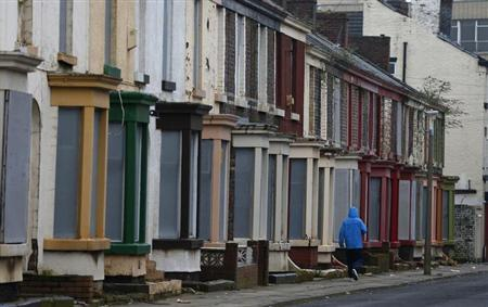A man walks past a row of boarded up terraced houses in the Kensington area of Liverpool, northern England February 20, 2013. REUTERS/Phil Noble
