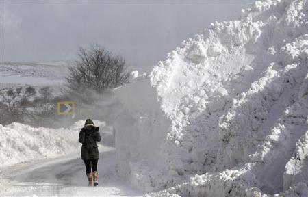A person walks past a snow drift on the Cushendall Road as wintry weather continues to cause havoc across the United Kingdom, in the Glens of Antrim, Northern Ireland March 24, 2013 REUTERS-Cathal McNaughton
