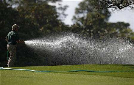 A member of the grounds crew waters the first fairway during a practice round in preparation for the 2013 Masters golf tournament at the Augusta National Golf Club in Augusta, Georgia, April 8, 2013. REUTERS/Brian Snyder