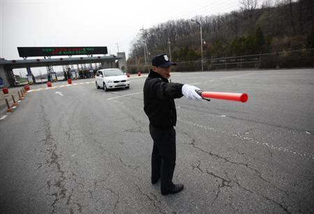 A South Korean security guard directs traffic as a vehicle transporting employees working at the Kaesong Industrial Complex (KIC) inside the North Korean border, passes through a gate at the South's CIQ (Customs, Immigration and Quarantine), just south of the demilitarised zone separating the two Koreas, in Paju, north of Seoul, April 8, 2013. REUTERS/Kim Hong-Ji