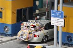 Подданные Южной Кореи покидают территорию промышленного комплекса, расположенного регионе Кэсон в КНДР, 8 апреля 2013 года. Северная Корея во вторник посоветовала находящимся в Южной Корее иностранным гражданам подумать об эвакуации на случай начала войны между двумя странами, переживающими в последние недели очередное обострение отношений. REUTERS/Kim Hong-Ji