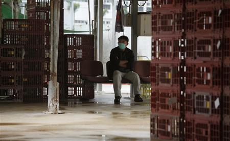 A worker rests beside empty cages, which were used to transport chickens, after morning trading at a wholesale poultry market in Hong Kong April 8, 2013. REUTERS/Bobby Yip