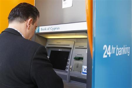 A man withdraws money from an ATM at a branch of Bank of Cyprus in Bucharest April 1, 2013. REUTERS/Bogdan Cristel
