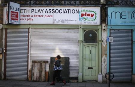 A woman walks past closed down shops in south London February 27, 2013. REUTERS/Andrew Winning