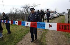 Полицейский на месте кровопролития в сербской деревне Велика-Иванча 9 апреля 2013 года. Ветеран войны с Хорватией расстрелял здесь 13 человек, включая свою мать и сына. REUTERS/Marko Djurica